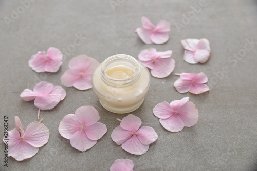 Plexiglas Spa Many Pink hydrangea petals with cream in bottle, on gray background