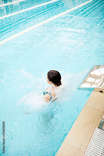 Young woman sitting in pool with jacuzzi effect in luxurious spa center or resort - 216614604