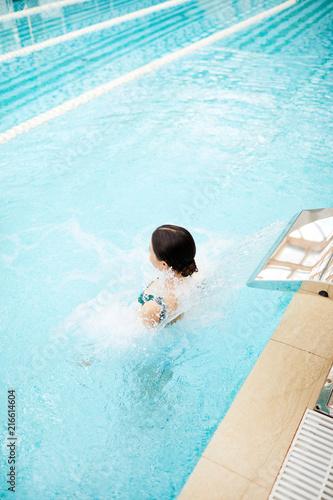 Młoda kobieta siedzi w basenie z jacuzzi efekt w luksusowym centrum spa lub ośrodek