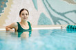 Quadro Young relaxed woman sitting in swimming-pool and enjoying time at spa center