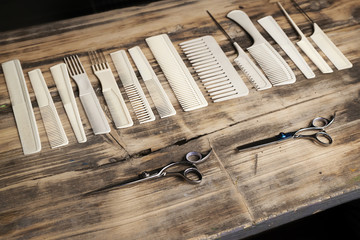 White plastic combs and scissors on old wooden table