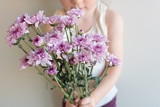cropped view of child holding purple chrysanthemum flowers (selective focus) - 216615650
