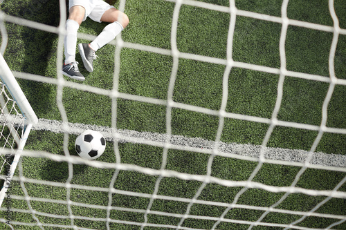 Fotobehang Voetbal Overview of soccer ball in gates by net and legs of goalkeeper lying on green field