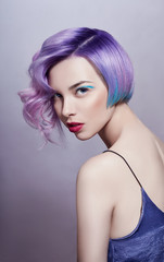 Portrait of a woman with bright colored flying hair, all shades of purple. Hair coloring, beautiful lips and makeup. Hair fluttering in the wind. Sexy girl with short  hair. Professional coloring © angel_nt