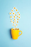 Yellow mug and chamomile flowers on a blue background. Chamomiles come out of the mug like steam.