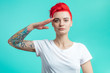Leinwandbild Motiv stylish woman with pink hair and tattoo doing a military. young awesome woman standing like a soldier isolated on the blue background