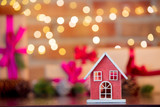 Wooden house toy on background with fairy lights in bokeh. Christmas Holiday season