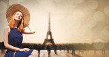 Young girl in dress and hat sitting at street with Parisian Eiffel tower on background. Image with bokeh and in vintage style