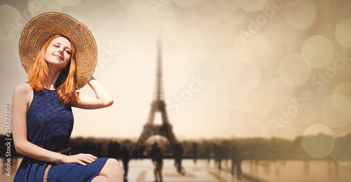 Wall mural Young girl in dress and hat sitting at street with Parisian Eiffel tower on background. Image with bokeh and in vintage style