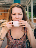 Young girl with white cup of coffee tea in cafe