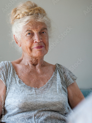 Plexiglas Kapsalon Portrait of elderly woman sitting in front of mirror looking at camera.