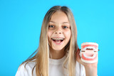 Young smiling girl with dental braces and teeth model on blue background