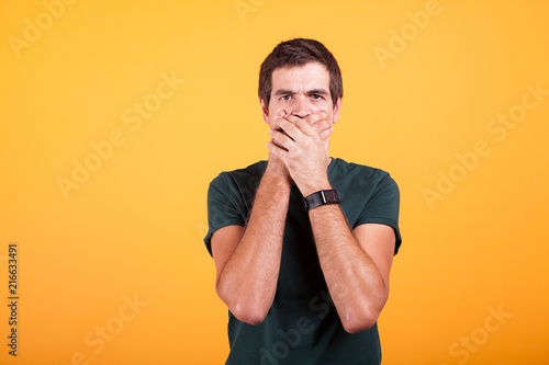 Foto Murales Attractive man in casual t-shirt covering his mouth in no talk sign on yellow background in studio photo.