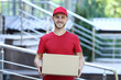 Leinwandbild Motiv Delivery man in red uniform with cardboard box