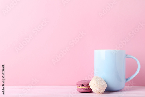 Foto Murales Cup of coffee with sweet macarons on pink background