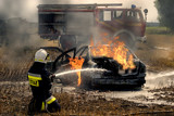 firefighter extinguishing a burning car that caught fire during an accident - 216635271
