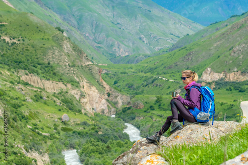 Foto Spatwand Olijf Young woman in the mountains with a backpack. Mountain landscape. River in the valley.