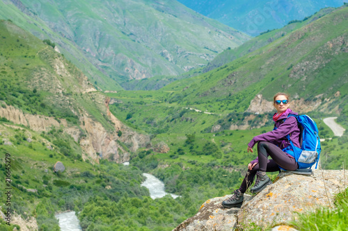 Aluminium Olijf Young woman in the mountains with a backpack. Mountain landscape. River in the valley.