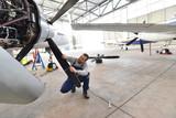 Mechaniker kontrolliert und repariert Flugzeug im Hangar // Airport workers check an aircraft for safety in a hangar