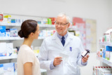 medicine, healthcare and people concept - senior apothecary with drugs and female customer at pharmacy - 216653271