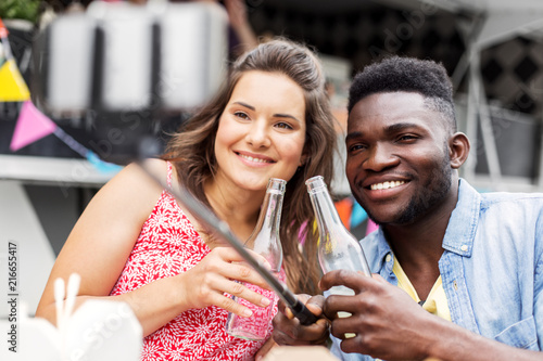 Leinwandbild Motiv leisure, technology and people concept - happy mixed race couple with drinks taking picture by selfie stick at food truck