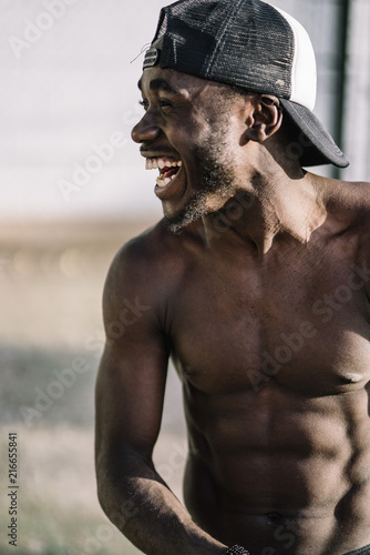 Foto Murales African man shows his muscular body to camera.