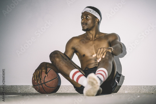 Foto Spatwand Basketbal African man poses with basketball in the street