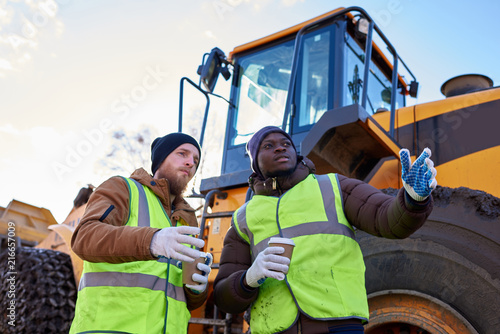 Foto Murales Low angle portrait of two workers, one African-American, drinking coffee and chatting standing next to heavy industrial truck on worksite