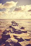 Vintage toned picture of a rocky breakwater at sunset.