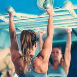 Female athlete doing pull-ups in the gym