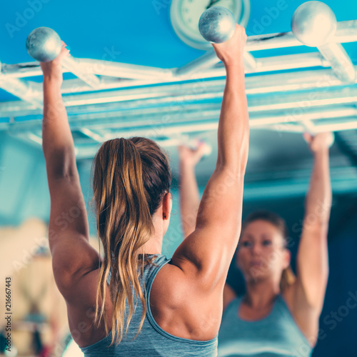 Plexiglas Fitness Female athlete doing pull-ups in the gym