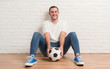 Leinwanddruck Bild - Young caucasian man sitting over white brick wall holding soccer football ball with a happy face standing and smiling with a confident smile showing teeth