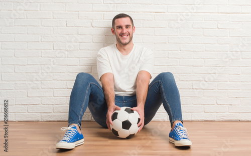 Leinwanddruck Bild Young caucasian man sitting over white brick wall holding soccer football ball with a happy face standing and smiling with a confident smile showing teeth