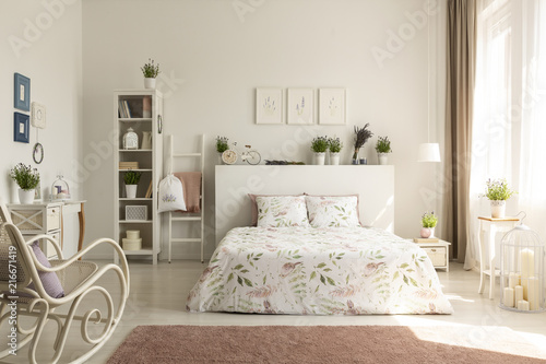 Real photo of a provencal bedroom interior with a double bed, floral sheets, shelves, plants and rocking chair © Photographee.eu