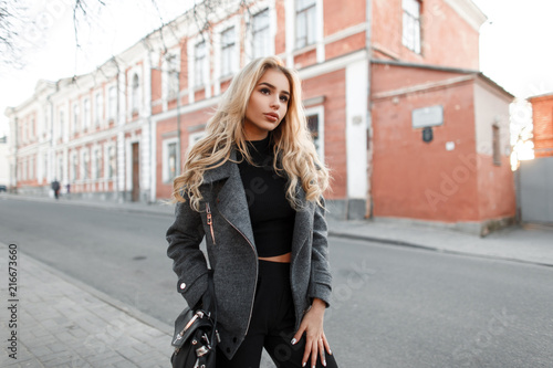 Leinwandbild Motiv Beautiful young woman model with a bag in a stylish gray jacket walking outdoors in the city