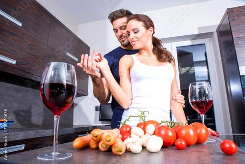 Leinwandbild Motiv Beautiful young couple in the kitchen