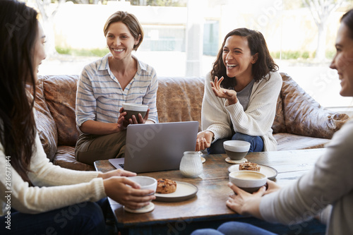 Four female friends talking over coffee at a coffee shop
