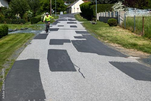 Foto Murales Vielfach ausgebesserte Straße in einer Gemeinde
