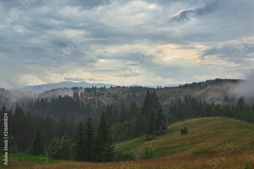 Cloudy evening in Carpathian forest and mountain landscape with small houses. foggy forest and cloudy sky in the Ukrainian mountains