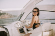 Quadro Young attractive woman drives a  yacht at sea