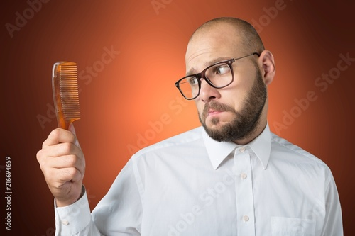 Leinwandbild Motiv Adult bald  man hand holding comb