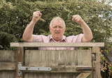 Mature man shouting and shaking his fists over a fence in the garden  - 216696638