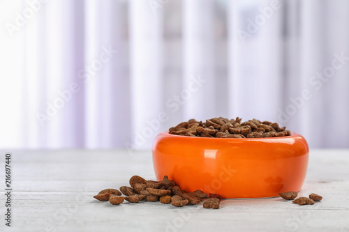 Bowl with food for cat or dog on floor. Pet care - 216697440