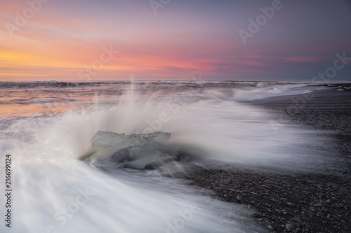 In de dag Zee zonsondergang Jokulsarlon beach at sunrise, long exposure photography with waves and pieces of ice on the black sand beach.