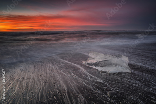 Fotobehang Zee zonsondergang Jokulsarlon beach at sunrise, long exposure photography with waves and pieces of ice on the black sand beach.