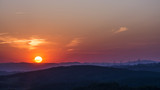 Sunset over the landscape with wind power plants. Sun tightly over the horizon.