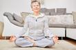 Leinwanddruck Bild - Seniorin im Lotossitz bei einer Yoga Übung