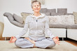 Leinwandbild Motiv Seniorin im Lotossitz bei einer Yoga Übung