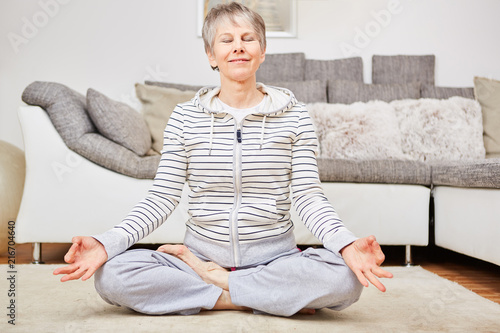 Leinwanddruck Bild Seniorin im Lotossitz bei einer Yoga Übung