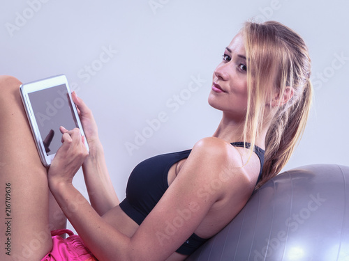 Plexiglas Fitness Fit woman sitting on floor with tablet pc